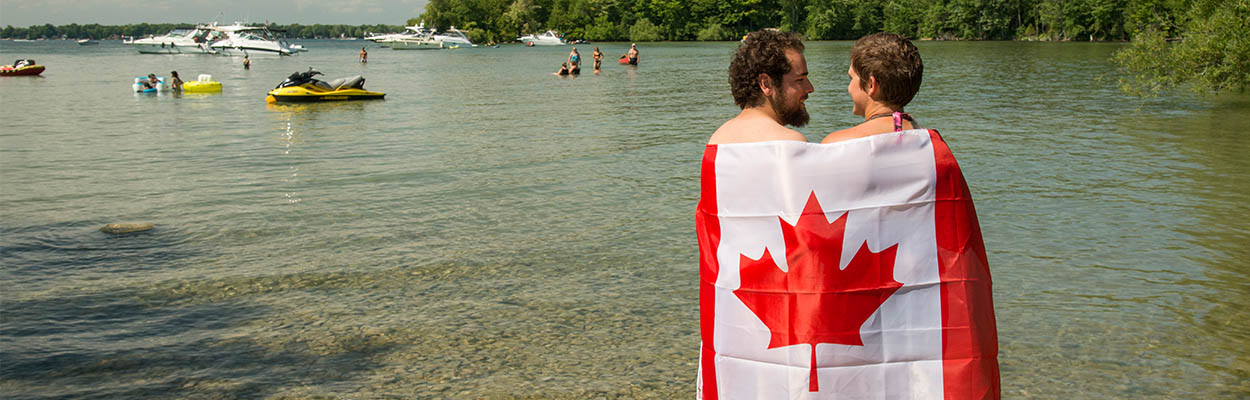 People With Flag 1250x400 - Canada Day Celebrations In Ontario's Lake Country