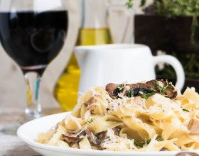 Pasta fettuccine with mushrooms and fried chicken ham in creamy cheese sauce on a light wooden background